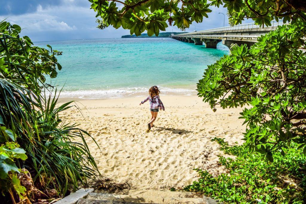 浜辺で腕を広げる女性