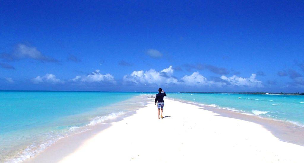 海へ続く砂浜を歩く女性